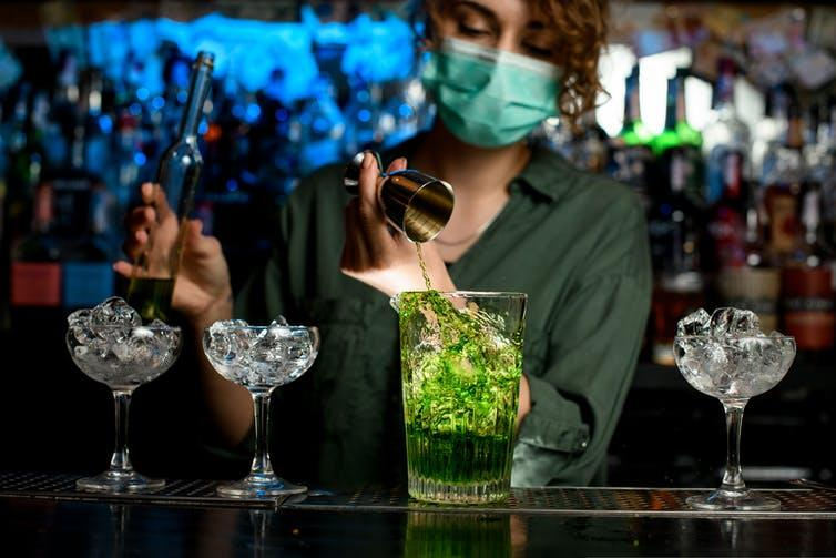 A bartender pours a cocktail while wearing a face mask.
