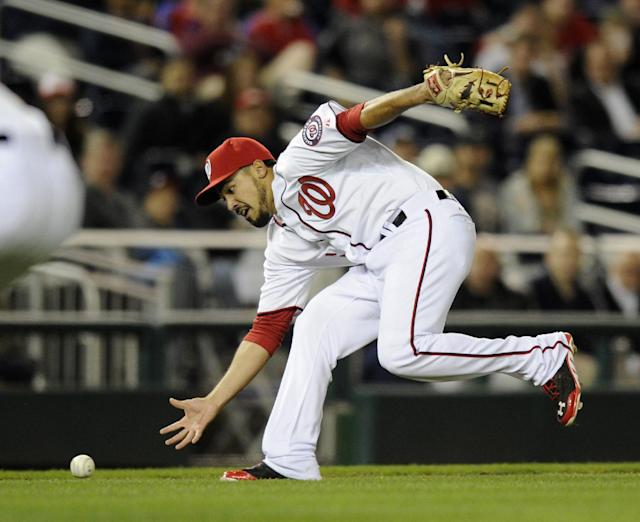 Washington Nationals third baseman Anthony Rendon fields a bunt by Miami Marlins' Reed Johnson during the seventh inning of a baseball game, Tuesday, April 8, 2014, in Washington. Johnson was out at first on the play. The Nationals won 5-0. (AP Photo/Nick Wass)