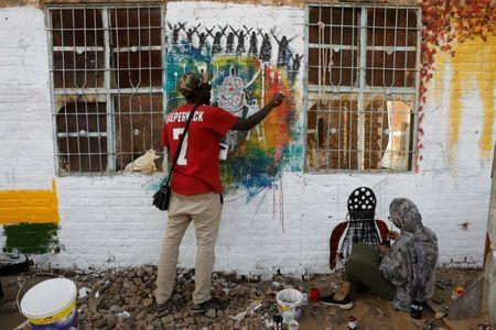 Sudanese people work on a mural near the defence ministry compound in Khartoum, Sudan, April 22, 2019. REUTERS/Umit Bektas