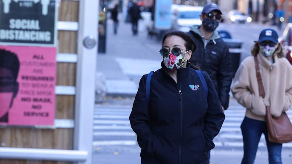 Pedestrians walk past a store with guidelines for social distance and face masks
