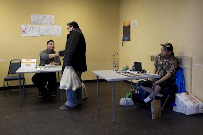 """In this Oct. 8, 2014 photo, manning an informational table at the entrance of the main general store in Barrow, Alaska, Gabe Tegoseak, left, meets a friend as he sits below handmade signs reading """"Are you a whaler?"""" and """"Vote Early."""" With much of the townspeople at the beach celebrating the catch of another whale, he's prepared for a light crowd. Tegoseak is working the ground game for Democratic Sen. Mark Begich. (AP Photo/Gregory Bull)"""