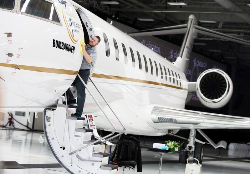 Bombardier employee polishes sign of Bombardier's Global 7500, the first business jet to have a queen-sized bed and hot shower, is shown during a media tour in Montreal