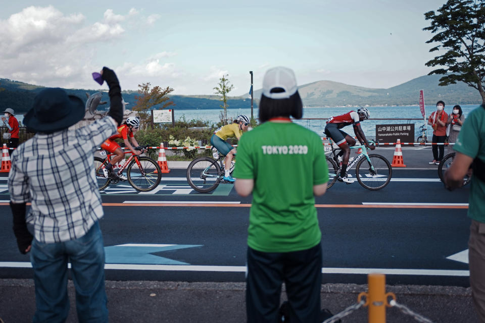 Fans watch as Teniel Campbell of Trinidad And Tobago (66), right, Amanda Spratt of Australia (18), and Jiajun Sun of China (61), compete during the women's cycling road race at the 2020 Summer Olympics, Sunday, July 25, 2021, in Oyama, Japan. (AP Photo/Thibault Camus)