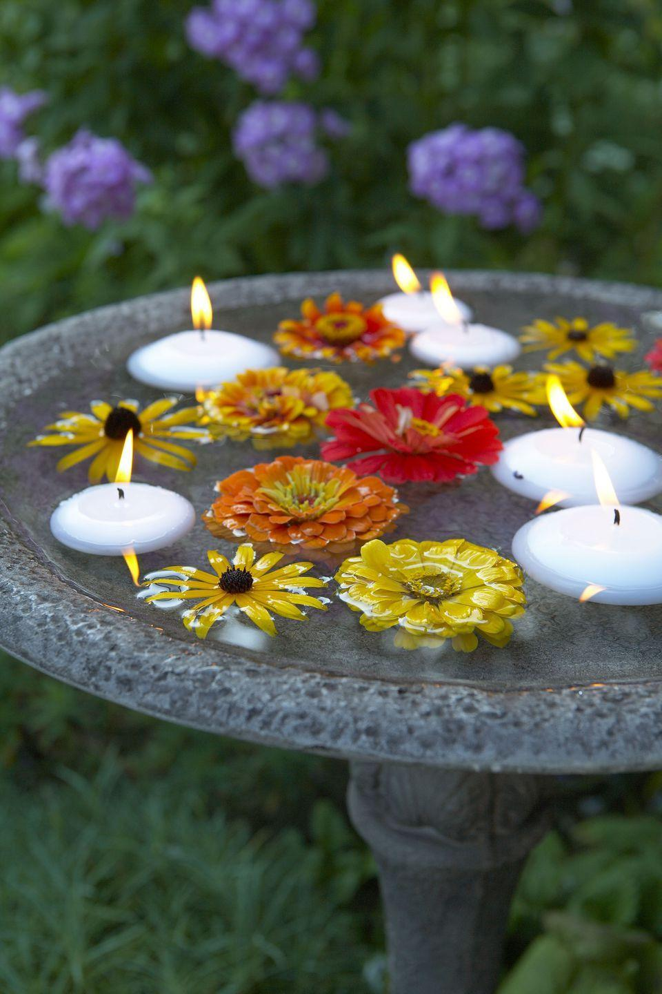 <p>Bobbing black-eyed Susans and zinnias, plus floating candles, turn an everyday birdbath into an instantly elegant water feature.</p>