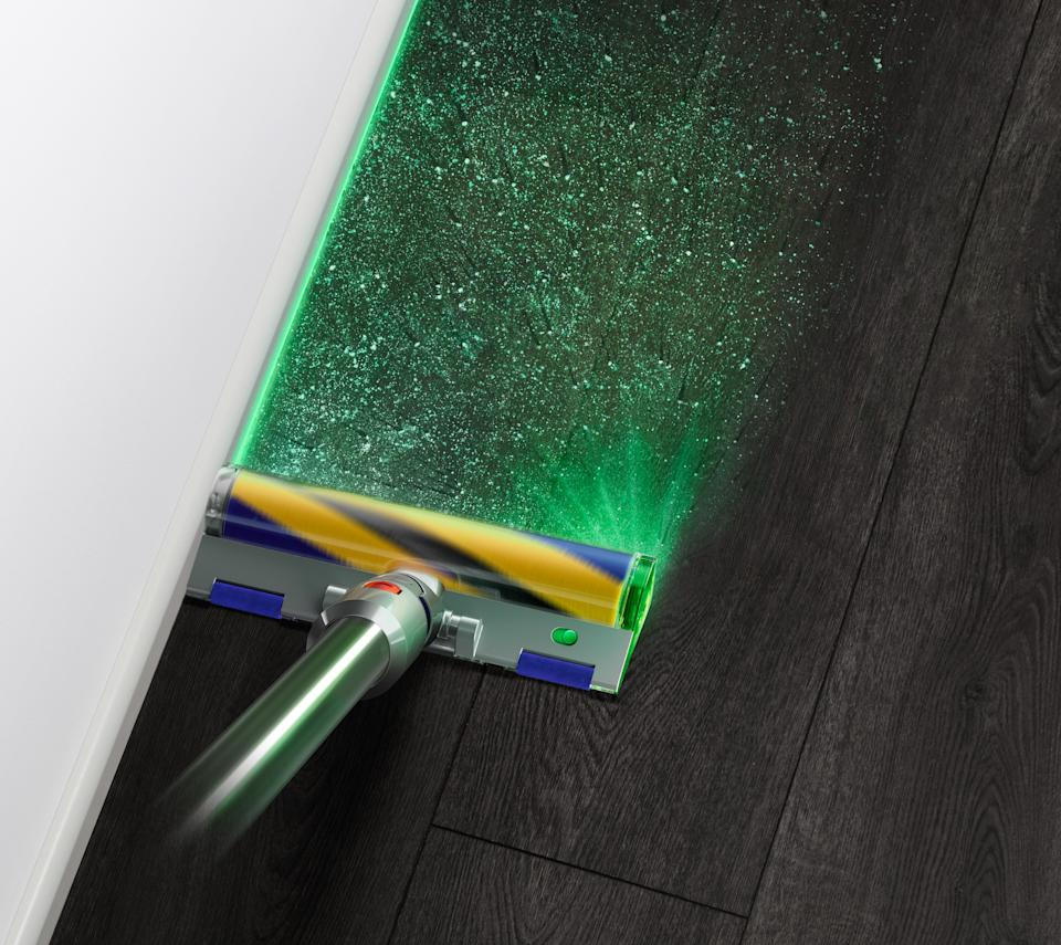 dyson v15 with laser on the fluffy head lighting up dust