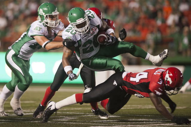 Saskatchewan Roughriders running back DeShawn Wynn is tackled during the second half of CFL pre-season football action against the Calgary Stampeders in Regina, Sask., Friday, June 22, 2012. The Stamps defeated the Riders 33-31. THE CANADIAN PRESS/Liam Richards