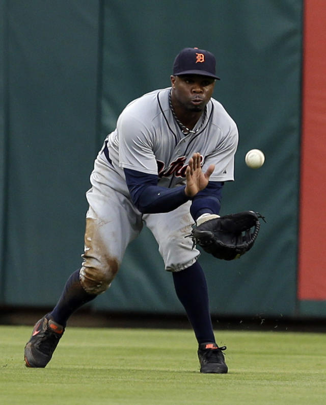 Detroit Tigers center fielder Rajai Davis reaches out and catches a fly ball by Texas Rangers' Elvis Andrus for the out in the first inning of a baseball game, Wednesday, June 25, 2014, in Arlington, Texas. (AP Photo/Tony Gutierrez)