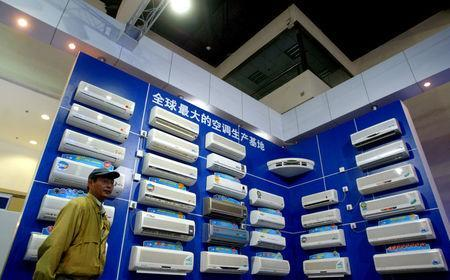 """FILE PHOTO: A man inspects China-made air-conditioners on display at a home appliance exhibition in Beijing May 9, 2004. The Chinese characters on the wall reads """"The world's biggest air-condition produce base"""". REUTERS/Wilson Chu/File Photo"""