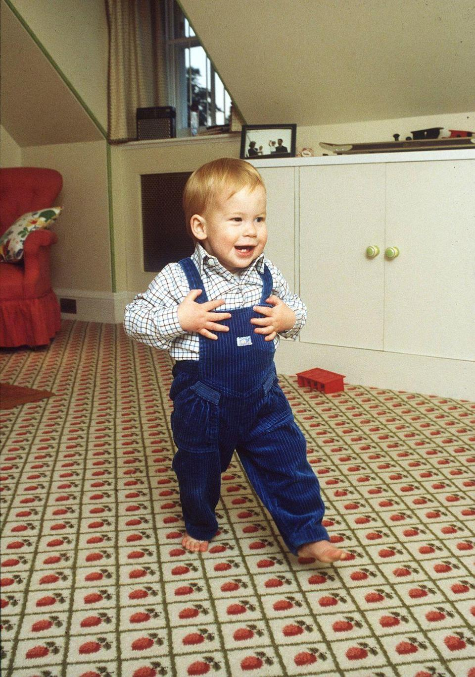 <p>Prince Harry takes his first steps in the playroom inside Kensington Palace not long after his first birthday. </p>