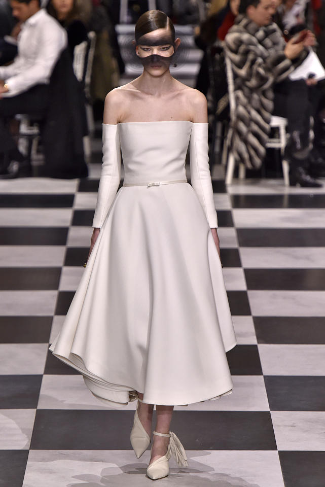 <p>Christian Dior's 2018 haute couture show in Paris featured designs inspired by surrealist artists like French poet André Breton. We can't see Markle in the black mask, but an off-the-shoulder gown would certainly be every bit modern bride, just like Markle. (Photo: Getty Images) </p>