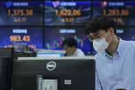 A currency trader watches monitors at the foreign exchange dealing room of the KEB Hana Bank headquarters in Seoul, South Korea, Friday, Oct. 15, 2021. Asian shares were higher Friday after technology companies powered the biggest gain on Wall Street since March. (AP Photo/Ahn Young-joon)