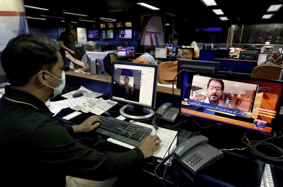 """Employees of Geo News television work at their office while a television channel broadcasts news regarding one their reporter Ali Imran Syed, missing in Karachi, Pakistan, Saturday, Oct. 24, 2020. The Geo bureau chief in Karachi said Saturday that police registered the journalist's disappearance as an """"abduction"""" case without naming suspects. (AP Photo/Fareed Khan)"""
