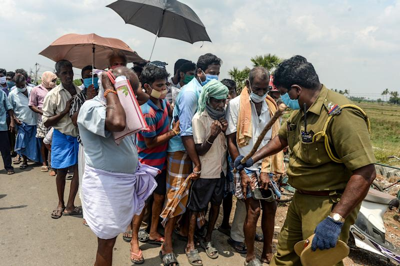A policeman (R) holding a stick regulates the crowd as people line up to buy alcohol at a liquor shop after the government eased a nationwide lockdown imposed as a preventive measure against the COVID-19 coronavirus, on the outskirts of Chennai on May 7, 2020. (Photo by Arun SANKAR / AFP) (Photo by ARUN SANKAR/AFP via Getty Images)