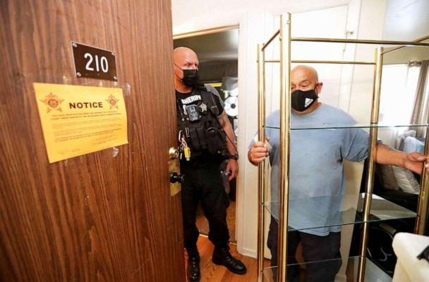 PHOTO: Milwaukee County Sheriff's Deputy Brian Green stands by as Rafael Hernandez, manager and truck driver with Eagle Movers and Storage Co., removes a shelf unit from an apartment during an eviction in Milwaukee, July 18, 2021. (Milwaukee Journal Sentinel via USA Today Network, FILE)