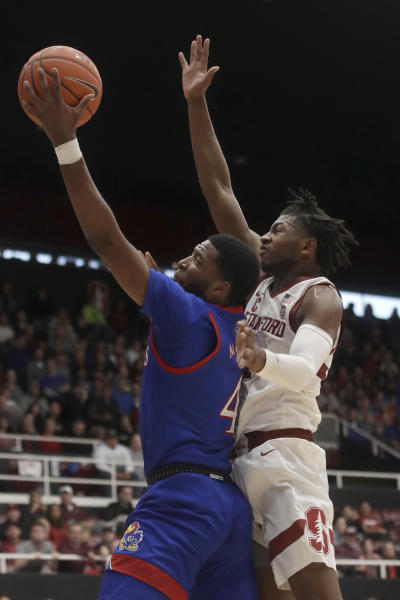 Kansas guard Isaiah Moss, left, shoots against Stanford guard Daejon Davis during the first half of an NCAA college basketball game in Stanford, Calif., Sunday, Dec. 29, 2019. (AP Photo/Jeff Chiu)