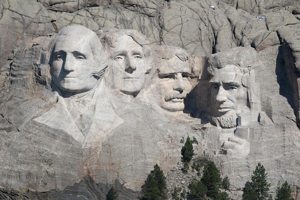 """<p>Mount Rushmore was crafted from raw materials, with workers carving 60-foot-tall heads of former U.S. presidents into the granite cliffs of South Dakota's Black Hills. A team of about 400 took roughly <a href=""""https://www.popularmechanics.com/technology/a23605/75-years-mount-rushmore/"""" rel=""""nofollow noopener"""" target=""""_blank"""" data-ylk=""""slk:14 years to complete"""" class=""""link rapid-noclick-resp"""">14 years to complete</a> the task, with no loss of life. During the process, workers primarily used dynamite to clear away 450,000 tons of rock, before carving the faces using facing bits and jackhammers.</p>"""