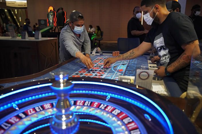FILE - In this July 4, 2020, file photo, people wear face masks as a precaution against the coronavirus as they play roulette on the Fourth of July at the Strat hotel-casino in Las Vegas. With the ongoing coronavirus pandemic curtailing tourism, visitors have found quiet gambling floors, shuttered showrooms and inexpensive rates. Some Las Vegas Strip casinos have been allowed to open at 100% capacity, officials said Tuesday, May 4, after showing Nevada state regulators that at least 80% of their employees have received at least one shot of coronavirus vaccine. (AP Photo/John Locher, File)
