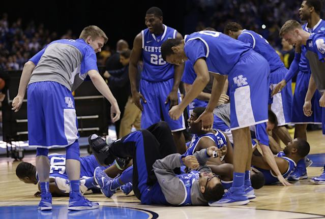 Kentucky players celebrate after an NCAA Midwest Regional final college basketball tournament game against Michigan Sunday, March 30, 2014, in Indianapolis. Kentucky won 75-72 to advance to the Final Four. (AP Photo/David J. Phillip)