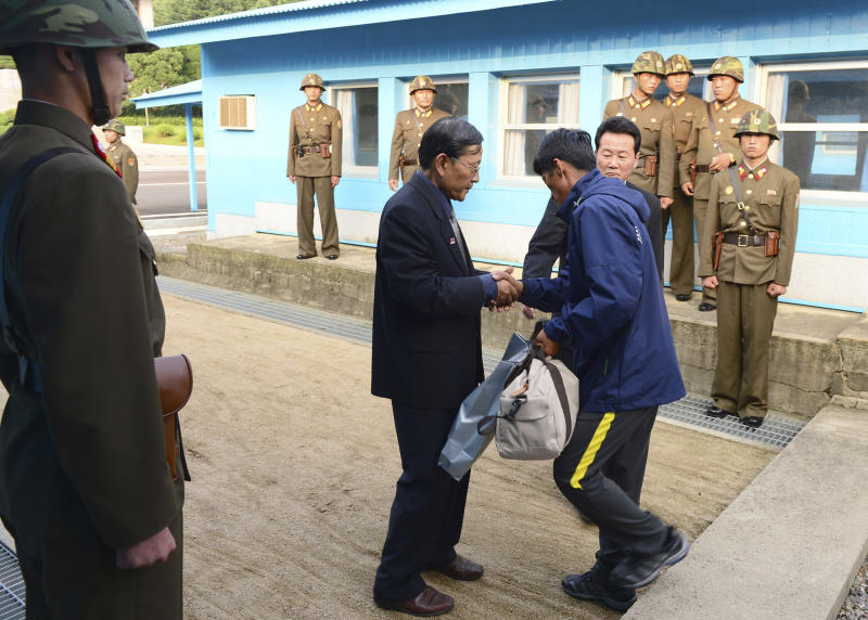 In this photo released by South Korea's Unification Ministry, a North Korean man, center right, is greeted by a North Korean official after returning from South Korea at the border village of Panmunjom, South Korea, Friday, July 6, 2013. South Korea repatriated three North Koreans rescued in South Korean waters aboard their drifting boat. (AP Photo/The Unification Ministry)