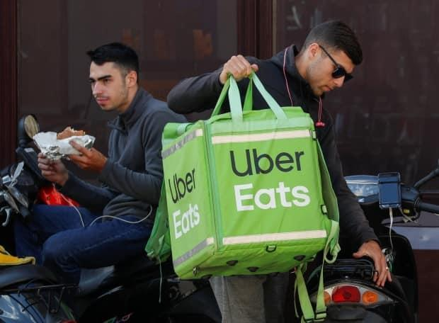 Services like Uber Eats and Skip the Dishes can take up to 30 per cent of an order's value, which can eat into the restaurant's profit margins.  (Valentyn Ogirenko/Reuters - image credit)