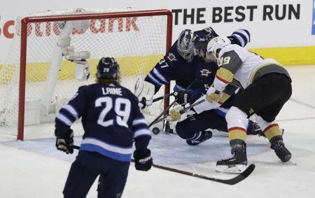 May 20, 2018; Winnipeg, Manitoba, CAN; Vegas Golden Knights right wing Alex Tuch (89) tries to get to the puck against Winnipeg Jets goaltender Connor Hellebuyck (37) and defenseman Dmitry Kulikov (5) in the second period in game five of the Western Conference Final of the 2018 Stanley Cup Playoffs at Bell MTS Centre. Mandatory Credit: James Carey Lauder-USA TODAY Sports