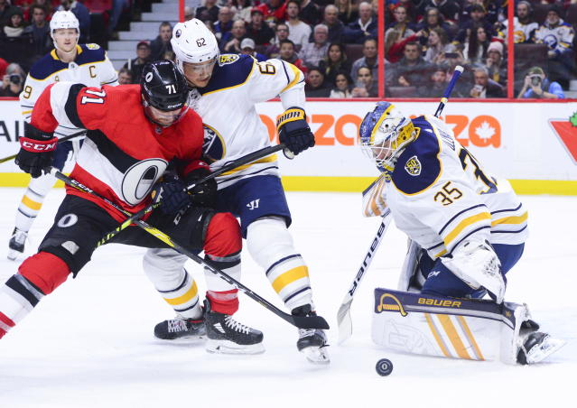 Buffalo Sabres goaltender Linus Ullmark (35) keeps his eyes on the puck as Buffalo Sabres defenseman Brandon Montour (62) holds off Ottawa Senators center Chris Tierney (71) during the second period of an NHL hockey game Monday, Dec. 23, 2019, in Ottawa, Ontario. (Sean Kilpatrick/The Canadian Press via AP)
