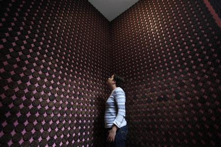 """A woman stands next to more than 2,000 chocolate samples adhered to the walls inside """"Mucho"""", a chocolate museum, in Mexico City"""