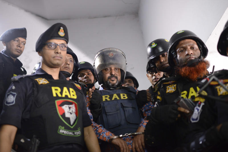 In this Oct. 6, 2019, photo, Bangladesh's ruling party member Ismail Hossain Chowdhury Samrat, accused of running a Dhaka casino empire and found with illegal drugs and liquor among other contraband, is escorted to a police station in Dhaka, Bangladesh. Security officials in Bangladesh are on the hunt for cash, gold and illicit weapons in a crackdown Prime Minister Sheikh Hasina ordered on illegal casinos, rooting out corruption among political elites that critics say has been allowed to flourish in a troubled democracy with no effective opposition.  So far the punishment for those convicted has been fairly light. Samrat, was expelled from the party and sentenced to six months in jail. For the crime of money laundering alone, he could have faced up to 12 years in prison. (AP Photo/Mahmud Hossain Opu)