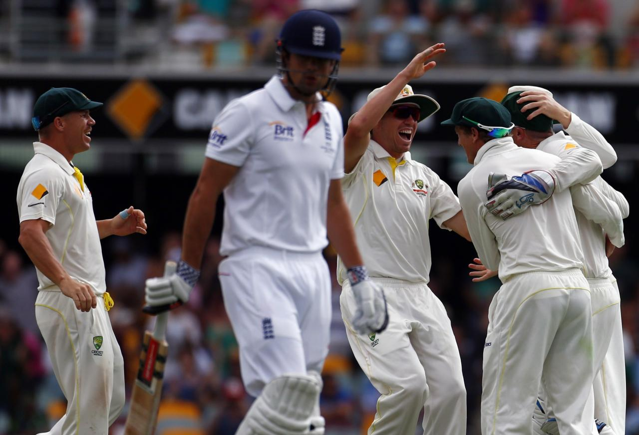 Australia's David Warner (L) and Peter Siddle celebrate with George Bailey (R) and Brad Haddin after taking the wicket of England's captain Alastair Cook during the fourth day's play of the first Ashes cricket test match in Brisbane November 24, 2013. REUTERS/David Gray (AUSTRALIA - Tags: SPORT CRICKET)