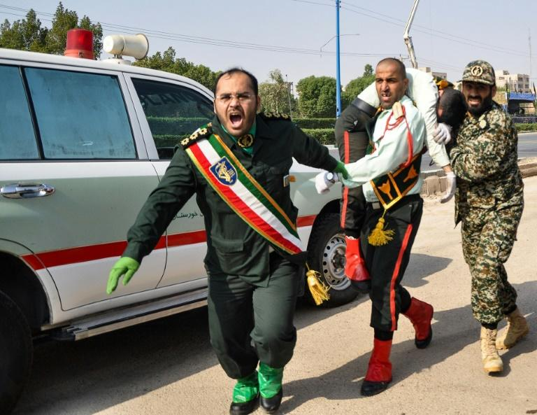 This picture taken on September 22, 2018 in the southwestern Iranian city of Ahvaz shows an Iranian soldier carrying an injured comrade at the scene of an attack on a military parade