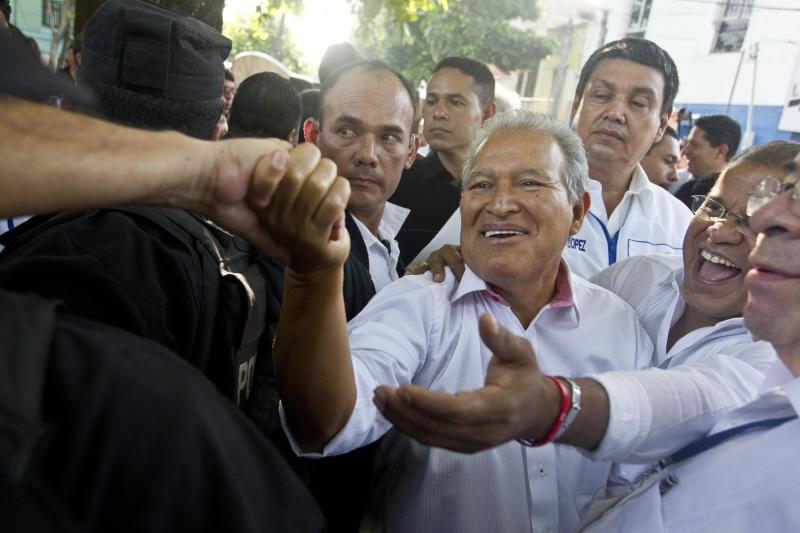 Presidential candidate Salvador Sanchez Ceren, the current vice president for the ruling Farabundo Marti National Liberation Front (FMLN), center, and his running mate Oscar Ortiz, right, greet supporters after casting their votes in the presidential runoff election in San Salvador, El Salvador, Sunday, March 9, 2014. Sanchez Ceren is running against former San Salvador Mayor Norman Quijano from the Nationalist Republican Alliance (ARENA). (AP Photo/Esteban Felix)