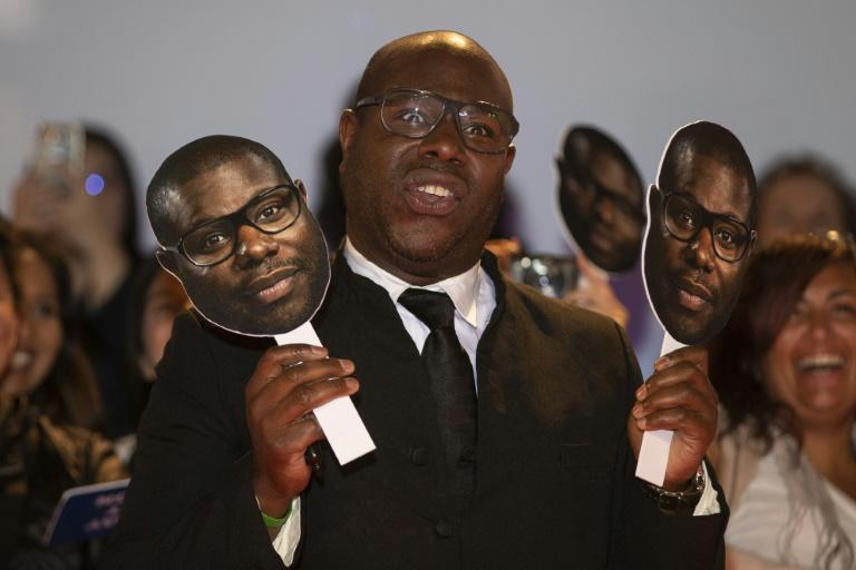British director Steve McQueen poses with photos of himself at the premiere of 'Widows' at the Toronto International Film Festival on September 8, 2018