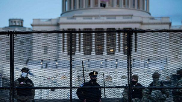 PHOTO: TOPSHOT - A Capitol police officer stands with members of the National Guard behind a crowd control fence surrounding Capitol Hill a day after a pro-Trump mob broke into the US Capitol on Jan. 7, 2021, in Washington, D.C. (Brendan Smialowski/AFP via Getty Images)
