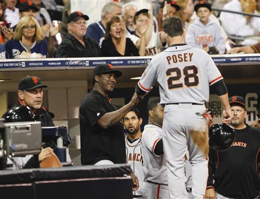 San Francisco Giants' Buster Posey is greeted at the dugout after scoring against the San Diego Padres during second inning of a baseball game Friday, Sept. 28, 2012 in San Diego. (AP Photo/Lenny Ignelzi)