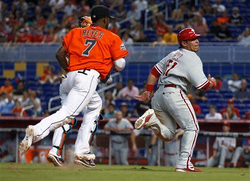 Philadelphia Phillies' Carlos Ruiz (51) looks over his shoulder before being tagged out by Miami Marlins' Jose Reyes (7) in a rundown during the eighth inning of a baseball game in Miami, Sunday, Sept. 30, 2012. The Phillies won 4-1. (AP Photo/J Pat Carter)