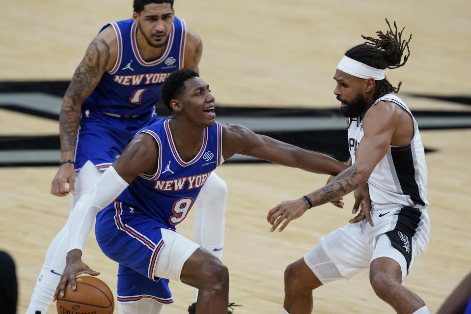 New York Knicks guard RJ Barrett (9) is defended by San Antonio Spurs guard Patty Mills (8) as he tries to move the ball up court during the second half of an NBA basketball game in San Antonio, Tuesday, March 2, 2021. (AP Photo/Eric Gay)