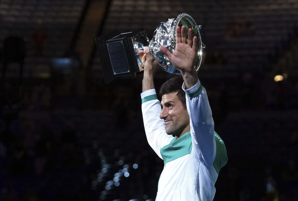 Serbia's Novak Djokovic holds the Norman Brookes Challenge Cup aloft after defeating Russia's Daniil Medvedev in the men's singles final at the Australian Open tennis championship in Melbourne, Australia, Sunday, Feb. 21, 2021.(AP Photo/Mark Dadswell)