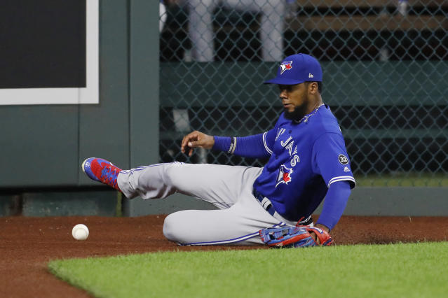 Toronto Blue Jays left fielder fielder Teoscar Hernandez slides on the warning track as he goes after a hit by Kansas City Royals' Hunter Dozier during the fourth inning of a baseball game at Kauffman Stadium in Kansas City, Mo., Thursday, Aug. 16, 2018. Dozier had an RBI double on the play. (AP Photo/Colin E. Braley)