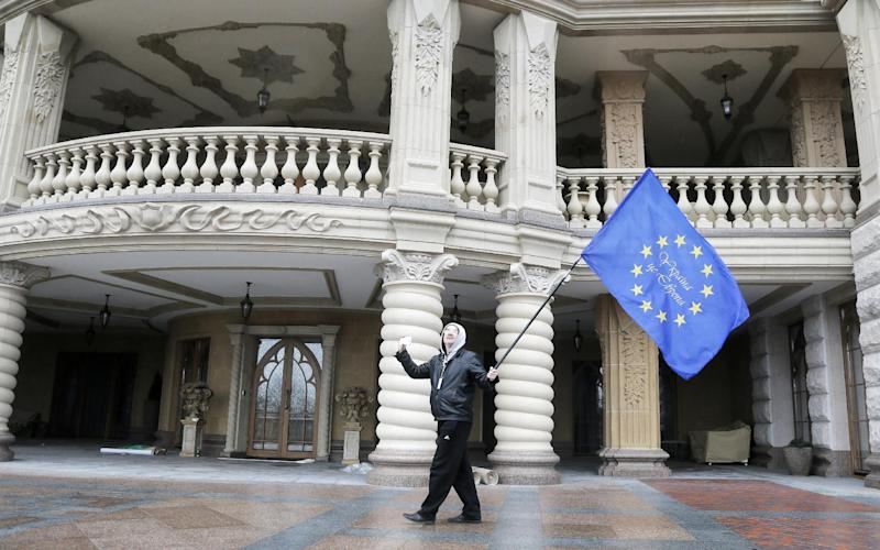 FILE - In this Saturday, Feb, 22, 2014, file photo, a protester waves an EU flag at Ukrainian President Viktor Yanukovych's country residence in Mezhyhirya, Ukraine. Ukrainians are getting an unfiltered look at the opulent lifestyle and alleged machinations of fugitive Yanukovych and his top officials from thousands of documents being posted online by journalists who say it's more important to record their country's history _ and document possible crimes _ than hold them back for their own scoops. Visitors to the YanukovychLeaks.org website can browse what appear to be the expense payments for running the sprawling compound just outside Kiev that reportedly was the Yanukovych's home. (AP Photo/Efrem Lukatsky, File)