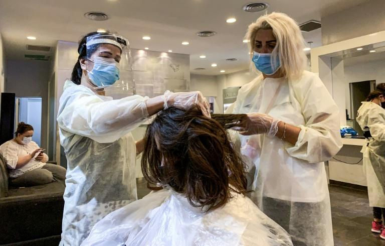 Hairdressers clad in face shield and mask cut a client's hair at a women's beauty centre in Saudi Arabia's capital Riyadh on June 21, 2020 (AFP Photo/RANIA SANJAR)