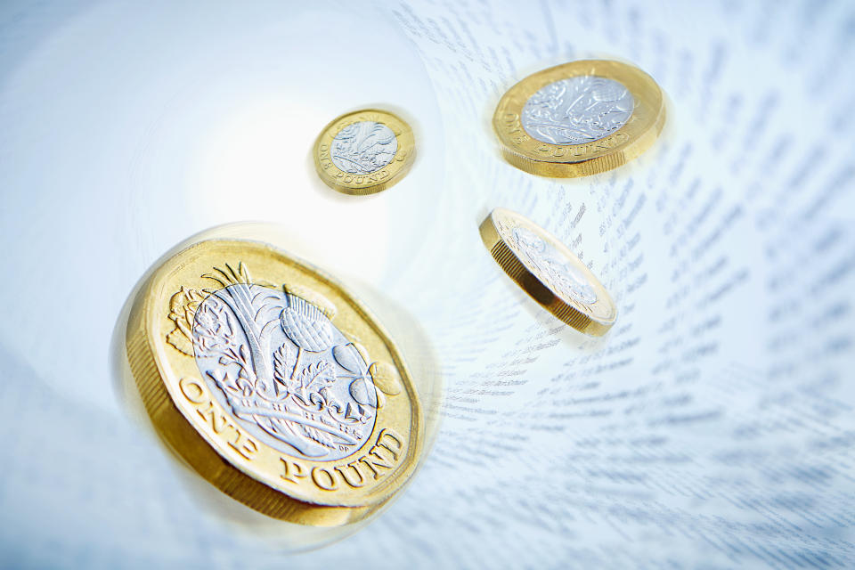One pound coins surrounded by stock market data