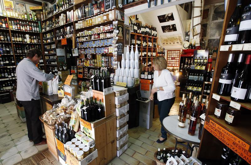 A customer keeps his purchases in a bag at a wine shop in Alella