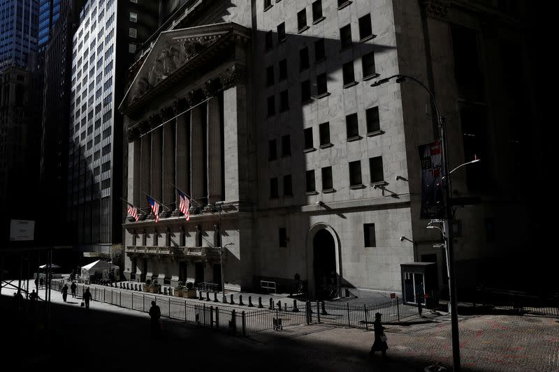 The New York Stock Exchange (NYSE) is seen as people walk in silhouette in the financial district of New York