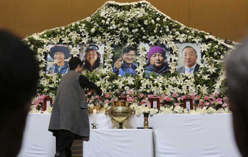 A mourner places a flower to pay tribute at a memorial altar for late South Korean mountain climbers at a university in Seoul, South Korea, Wednesday, Oct. 17, 2018. Relatives dressed in black funeral suits wept in grief on Wednesday as the bodies of five South Korean mountain climbers arrived home from Nepal where they had died in a storm last week. (AP Photo/Ahn Young-joon)