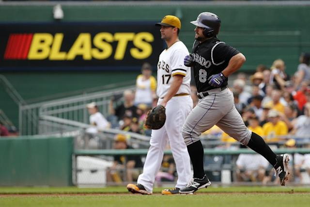 Colorado Rockies' Michael McKenry (8) rounds first past Pittsburgh Pirates first baseman Gaby Sanchez (17) after hitting a solo home run off Pittsburgh Pirates starting pitcher Jeff Locke during the second inning of a baseball game in Pittsburgh, Sunday, July 20, 2014. (AP Photo/Gene J. Puskar)