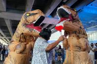 Dinosaur costumed actors representing Thailand's establishment at a high school student led protest in Bangkok