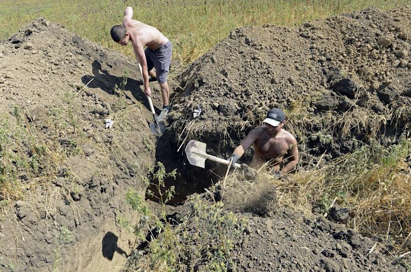 Residents of Mariupol dig trenches as they assist Ukrainian troops in organising their defence on the outskirts of the southern Ukrainian city of Mariupol on August 29, 2014