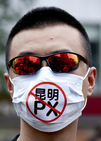 """A Chinese man wears a face mask with the word """"No to Kunming PX,"""" paraxylene, written on, takes part in a protest against a planned refinery project in downtown Kunming in southwest China's Yunnan province Saturday, May 4, 2013. After word spread about an environmental protest that was planned for Saturday in the central Chinese city of Chengdu, drugstores and printing shops were ordered to report anyone making certain purchases. Microbloggers say government fliers urged people not to demonstrate, and schools were told to stay open to keep students on campus. Meanwhile, hundreds of people - many wearing mouth masks - gathered in Kunming to protest a planned refinery project in the area. The demonstrators demanded information transparency and that public health be safeguarded. (AP Photo) CHINA OUT"""