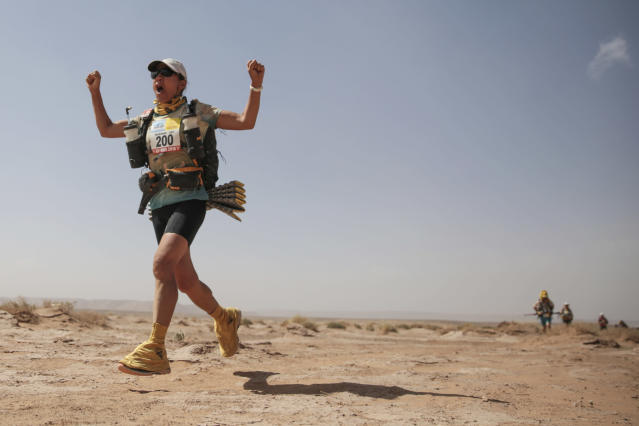 A competitor gestures as she approaches a checkpoint, while taking part in stage 5 of the 33rd edition of Marathon des Sables, in the Sahara desert, near Merzouga, southern Morocco, Friday, April 13, 2018. (AP Photo/Mosa'ab Elshamy)