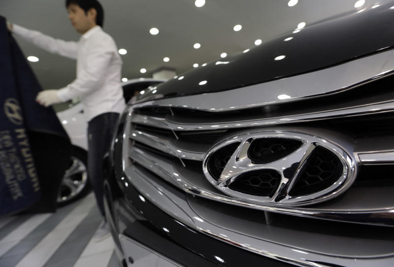 A man removes a carpet to clean near a Hyundai Motor's car on display at the company's showroom in Seoul, South Korea, Thursday, Oct. 25, 2012. Hyundai Motor Co. suffered a fall in third quarter profit versus the previous quarter after strikes dented vehicle production. (AP Photo/Lee Jin-man)